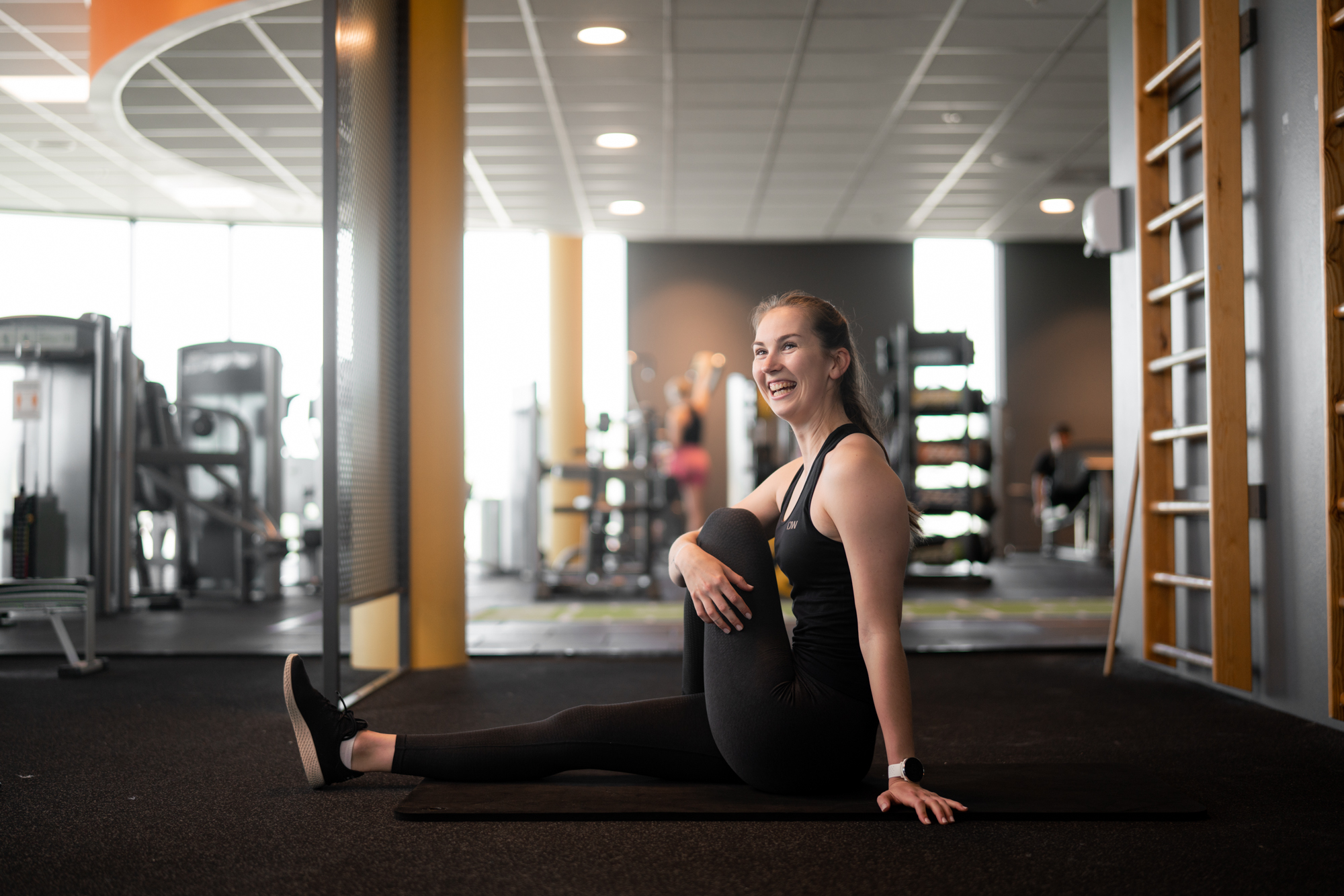 Girl stretching and smiling on the ground at Impulse fitness centre